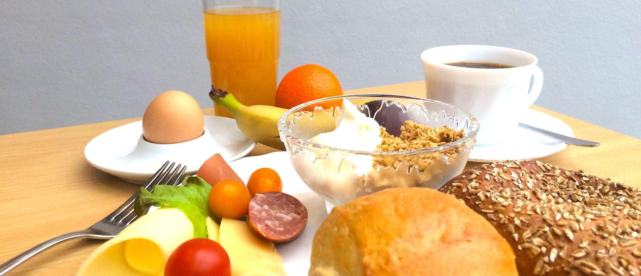 Üppiges Frühstück mit Kaffee, Brötchen, Marmelade, Käse, Wurst und mehr